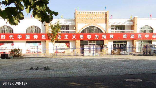 關押維吾爾族婦女的教育轉化營外圍懸掛著中共宣傳標語