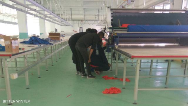 一大型廠房內工人正在調試機器