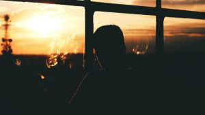 男子通過窗戶看夕陽