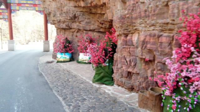 七步溝景區內的羅漢雕像被綠布包裹起來,周身被插上花(知情人提供)