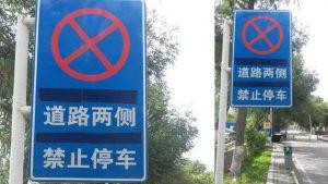 烏魯木齊市的新疆大學校園內「道路兩側禁止停車」的路標,上面的維語譯文已被用膠帶蓋住。
