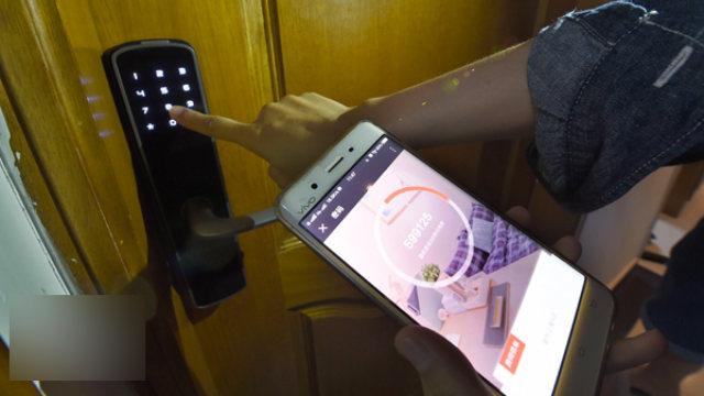 工人正在用手機App測試智能門鎖(網絡圖片)