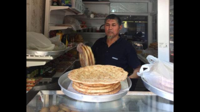 這位來自喀什的師傅正自豪地展示剛從烤爐中新鮮出爐的nan餅。