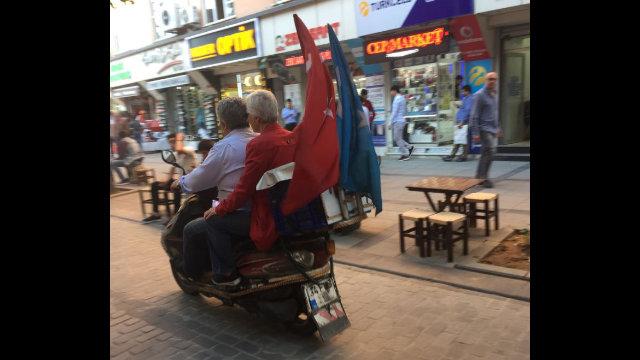 騎著摩托車的維吾爾人,他們的車尾飄著土耳其國旗和東突厥斯坦國旗。