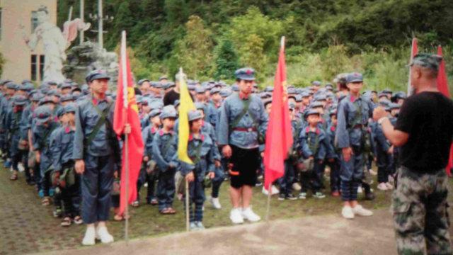 一群學生身穿紅軍服頭戴紅軍帽,背著印有毛主席頭像的包,上面寫著為人民服務。(微信圖片)