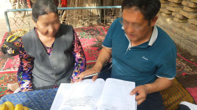 新疆某地政府人員正在讓老婦人看資料(網絡圖片非当事人)