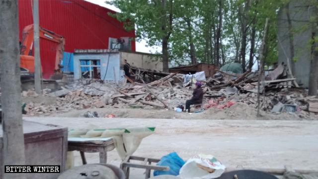 駐馬店市一位老婦人坐在被拆的房屋廢墟旁