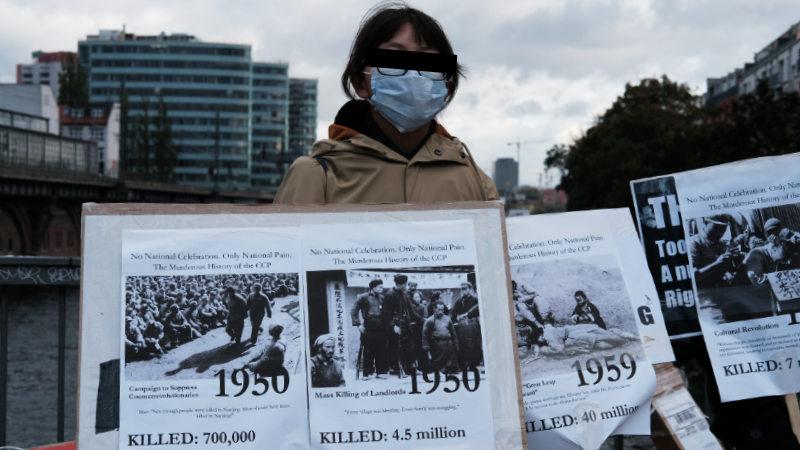 一名年輕女孩展示中共自執政以來殘殺中國人民的數據,揭中共累累罪行。(志願者提供)
