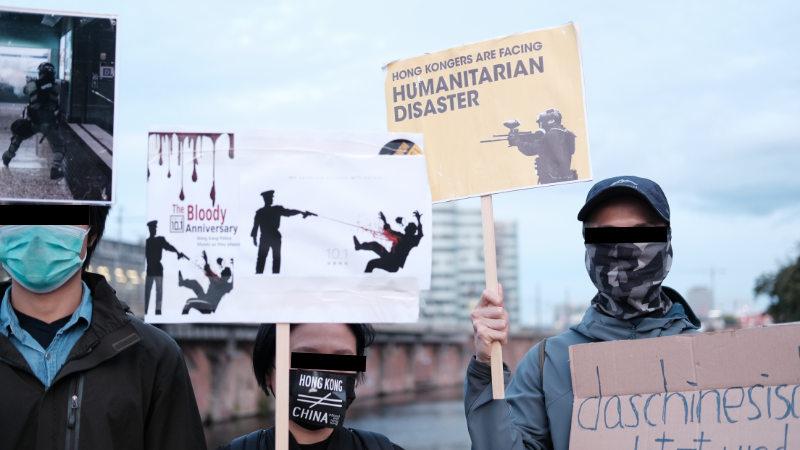 在德港人舉牌控訴香港警察向示威者開槍(志願者提供)