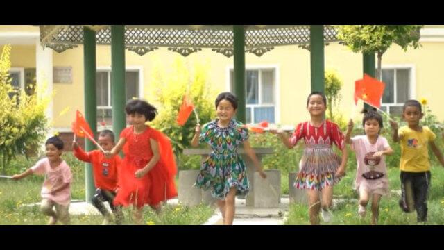 中共的宣傳——「快樂的」維吾爾兒童揮舞著中國國旗。