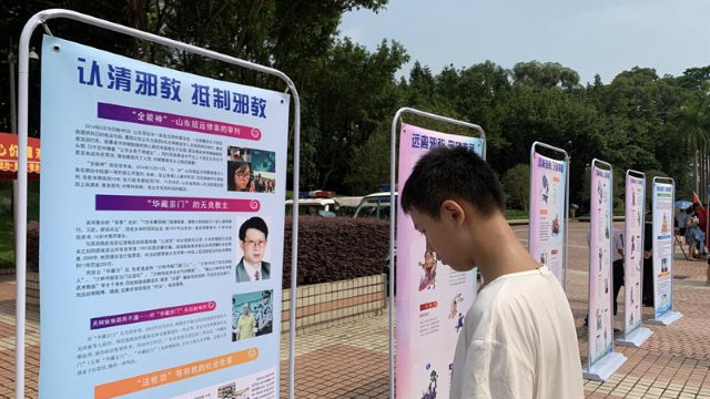 廣東省廣州市某社區內,一少年正在瀏覽反「邪教」宣傳圖片展。(網絡圖片)