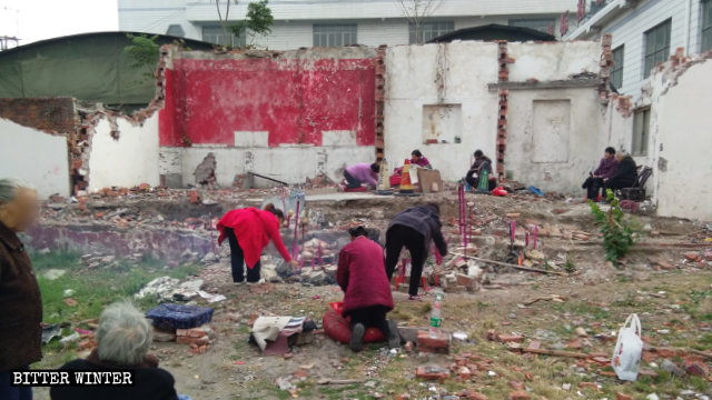 老年信徒在廢墟中祭拜