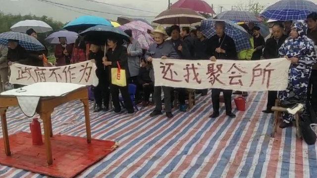 信徒拉著控訴政府的橫幅在被拆的聚會所遺址上聚會(知情人提供)