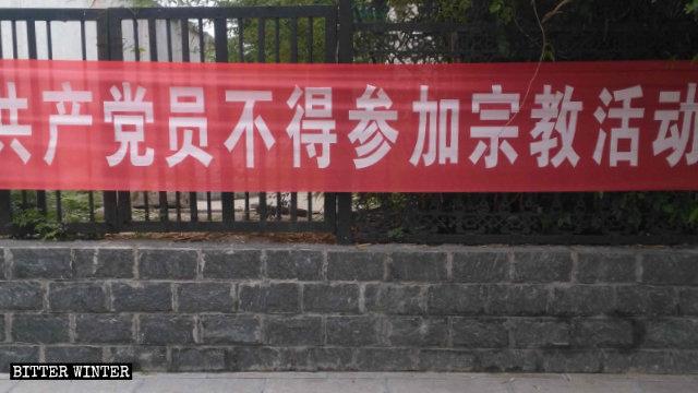 河南輝縣市上八里鎮掛的共產黨員不得參加宗教活動的橫幅