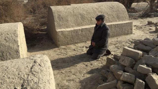 但是2012年,在墓地還沒被拆毀的時候,阿齊茲跪在他家人的墓地前面的照片證實了中共媒體在說謊。