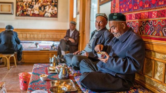 中共宣傳機構的炒作:一張維吾爾人坐在咖啡店裡的舊照片成了證明新疆祥和美好的「證據」