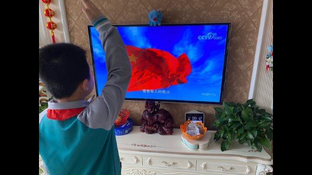 山東膠州小學生在家通過電視機上網課觀看升國旗並敬禮(網絡圖片)