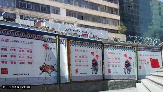 一佈滿了鐵絲網的圍牆上懸掛著習近平「中國夢」的宣傳海報