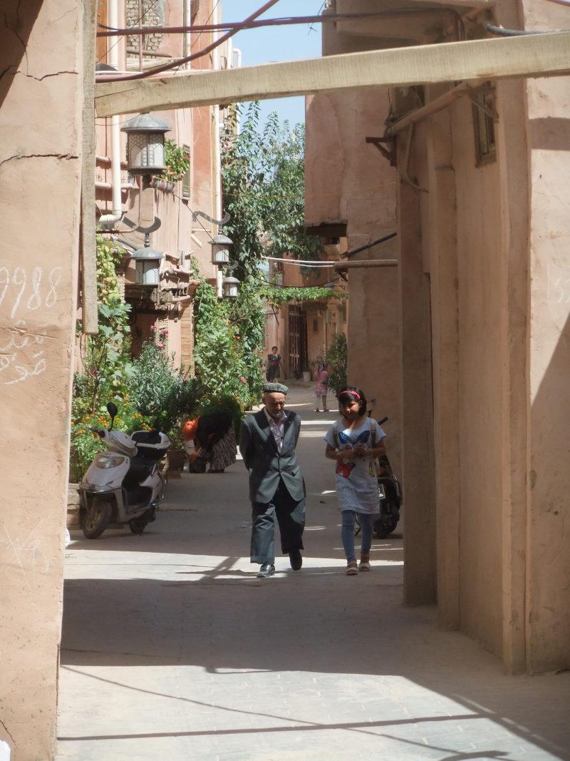 一位老人正從改造後的自家小巷的台階上往下走。喀什 2016年