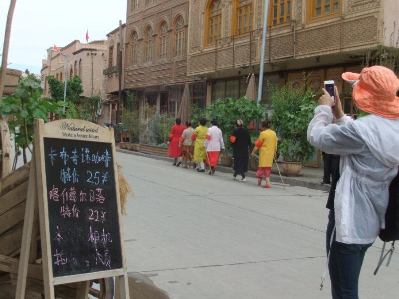 漢族遊客在欣賞「民族特色」景色,維族防護隊正從旁邊走過。維族人被徵募,互相監控,巡邏自己的居住區。喀什 2018年