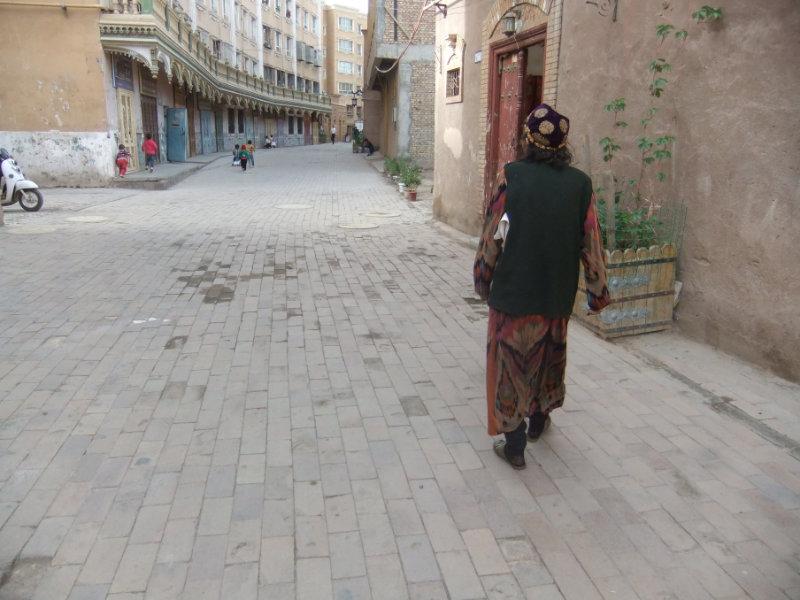 一名老年維吾爾族婦女正走在重建、拓寬後的大路上。現在諷刺的是她不得不戴維吾爾族花帽,而不是她的頭巾。這種帽子一般是年輕女孩或婦女的打扮,而頭巾當下則被視為忠實於「極端」伊斯蘭教的象徵。喀什 2018年