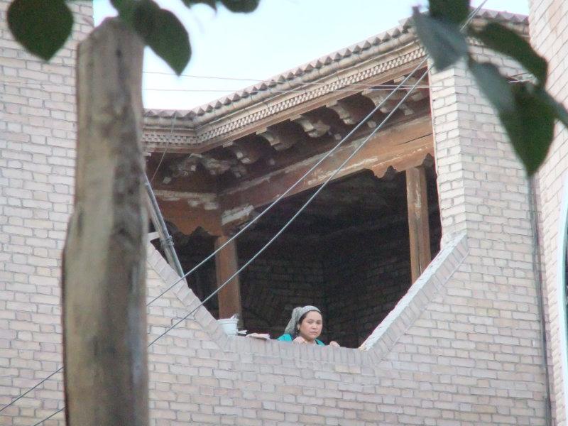 一婦人正從由水泥和磚改建後的家裡往外看。喀什 2012年