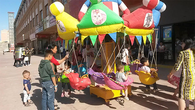 2018年,幾個母親帶著孩子們在和田一條商業街上玩耍。背後有奉政府命令每天多次巡邏、高度警惕的「家鄉防衛隊」(露絲·英格拉姆攝)