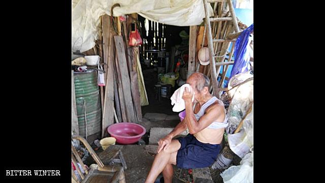 一位八旬老人坐在自己的住棚外