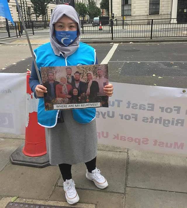 迪麗娜孜手裡拿著她伯父叔叔們的照片,他們全被中共關進了監獄
