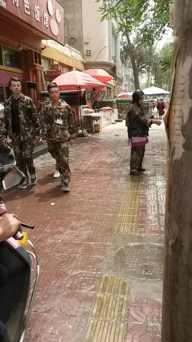 高中生做好了行動準備,他們路過一間餐館,餐館老闆穿好了服裝預備在和田的大街上殺敵(圖片由露絲·英格拉姆拍攝)